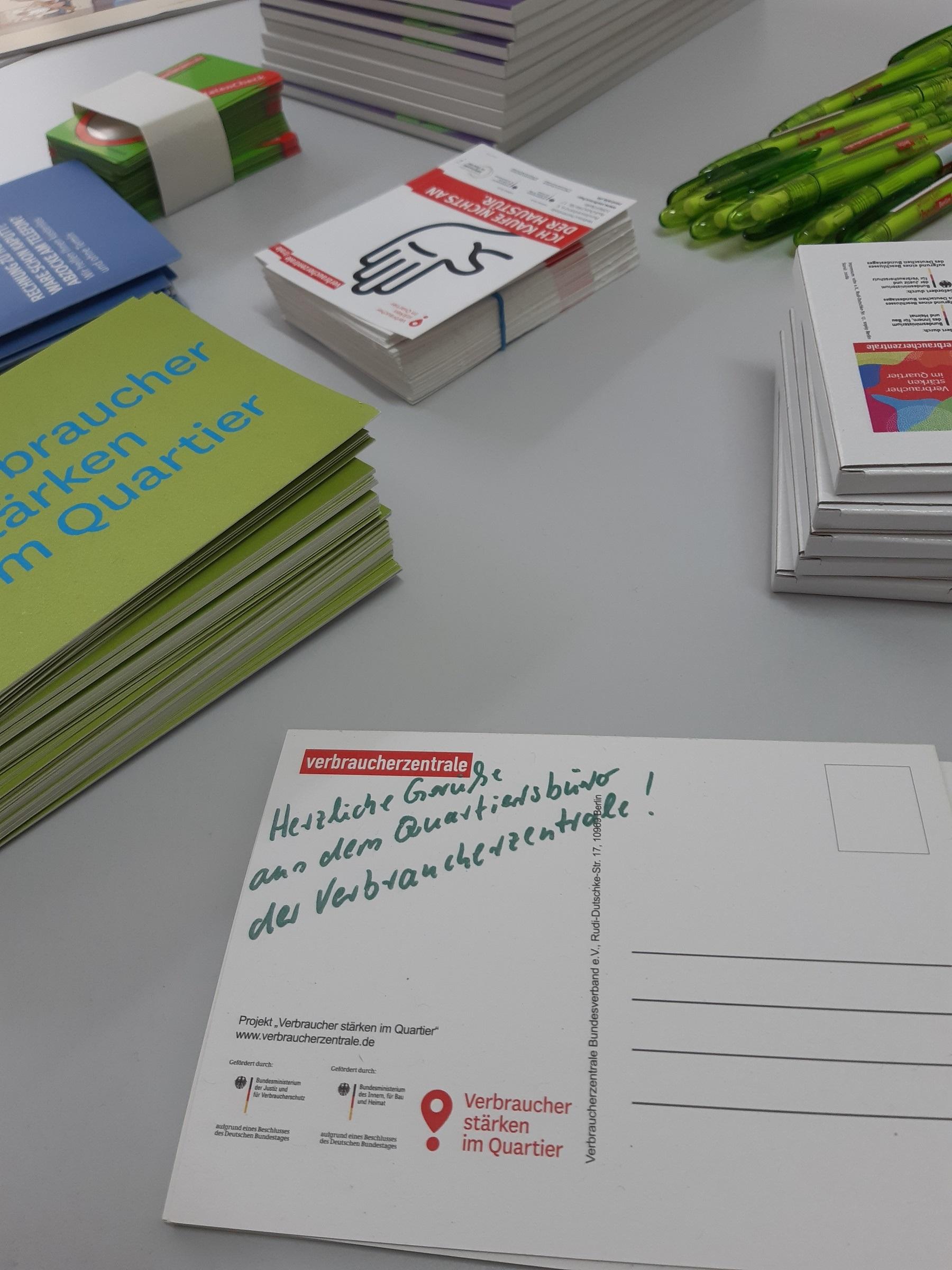 ein Tisch auf dem verschiedenes Werbematerial der Verbraucherschützer liegt, zB Kugelschreiber, Flyer, Postkarten