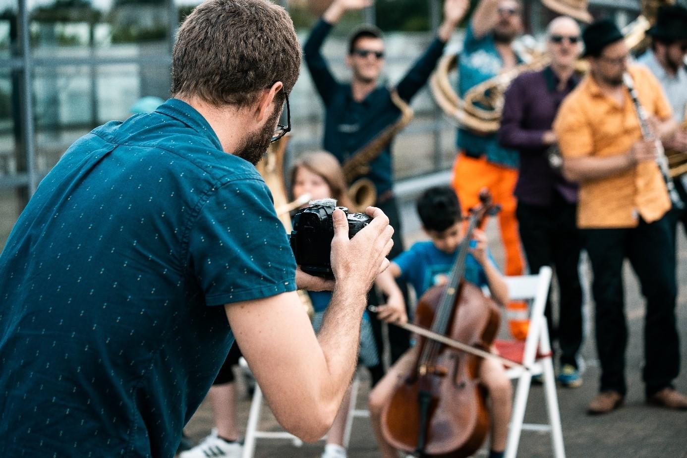 ein Mann von Hinten, wie er Foto und Filmaufnahmen von anderen Menschen macht, die tanzen oder Musik spielen (unscharf)