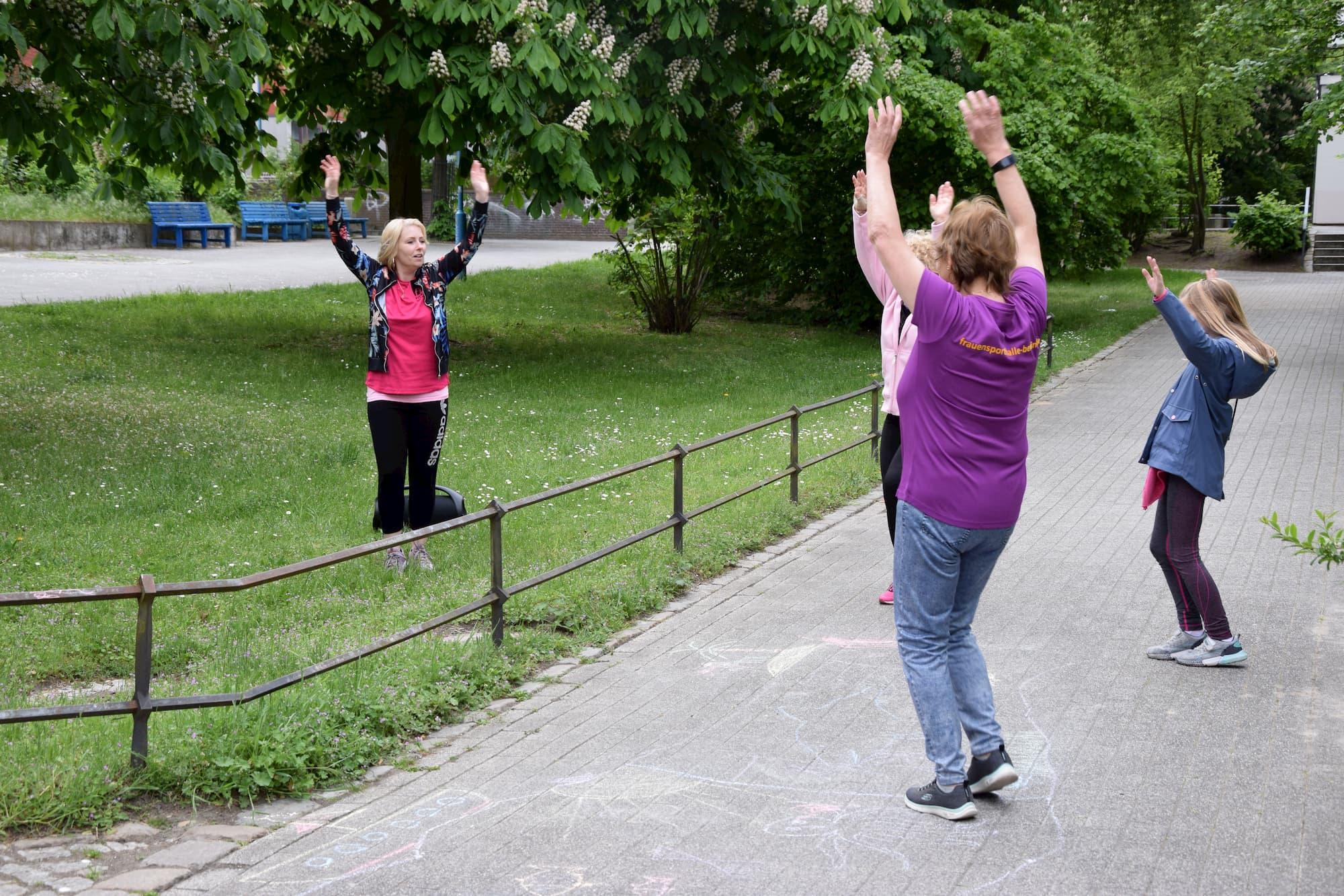 Eine gemischte Gruppe macht gemeinsam Sport im Park und streckt die Hände nach oben. Es sind 3 Frauen und 1 kleines Mädchen im Grundschulalter zu sehen