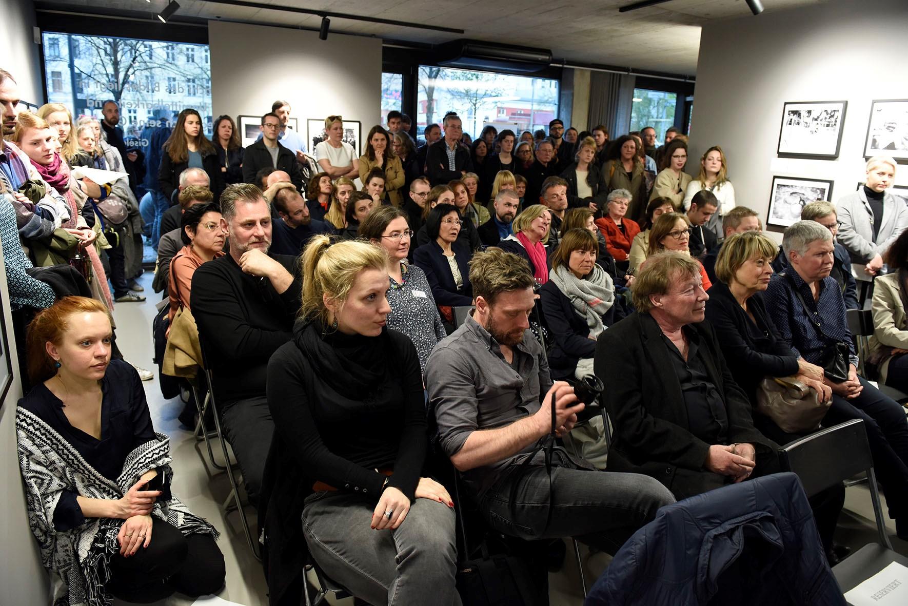 Publikum der Veranstaltung. Der Raum ist gut gefüllt, einige Personen stehen hinter und seitlich der Bestuhlung.