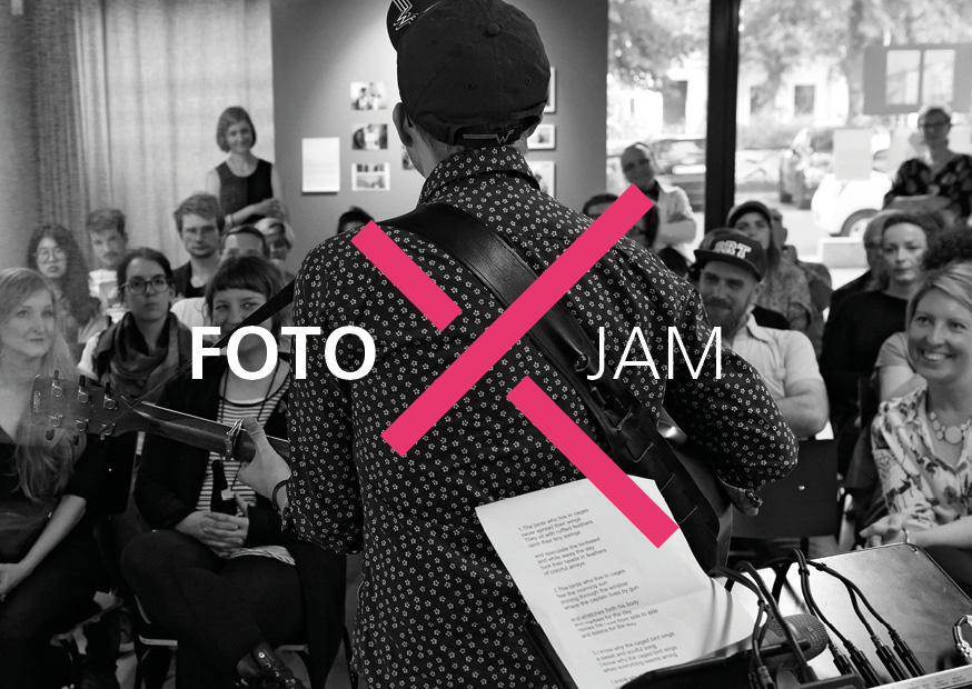 """Sänger mit Gitarre, von hinten fotografiert. Hinter ihm sieht man das Publikum. Das Logo der Veranstaltung, ein rotes X inzwischen der Namens """"Foto Jam"""", ist darüber gelegt. Das Bild im Hintergrund ist schwarz-weiß gehalten."""