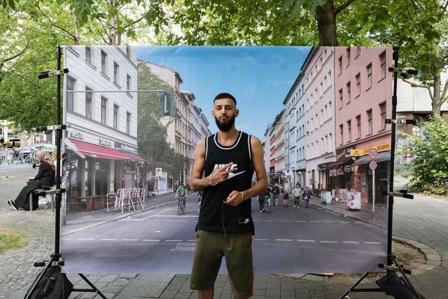 Junger Mann im Tanktop posiert vor der Leinwand und zeigt das Peace-Zeichen.