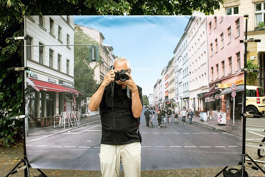 Ein älterer Mann posiert vor der Leinwand. Er hält seine Kamera vor dem Gesicht, als würde er ein Bild der ihn fotografierenden Fotografin machen.