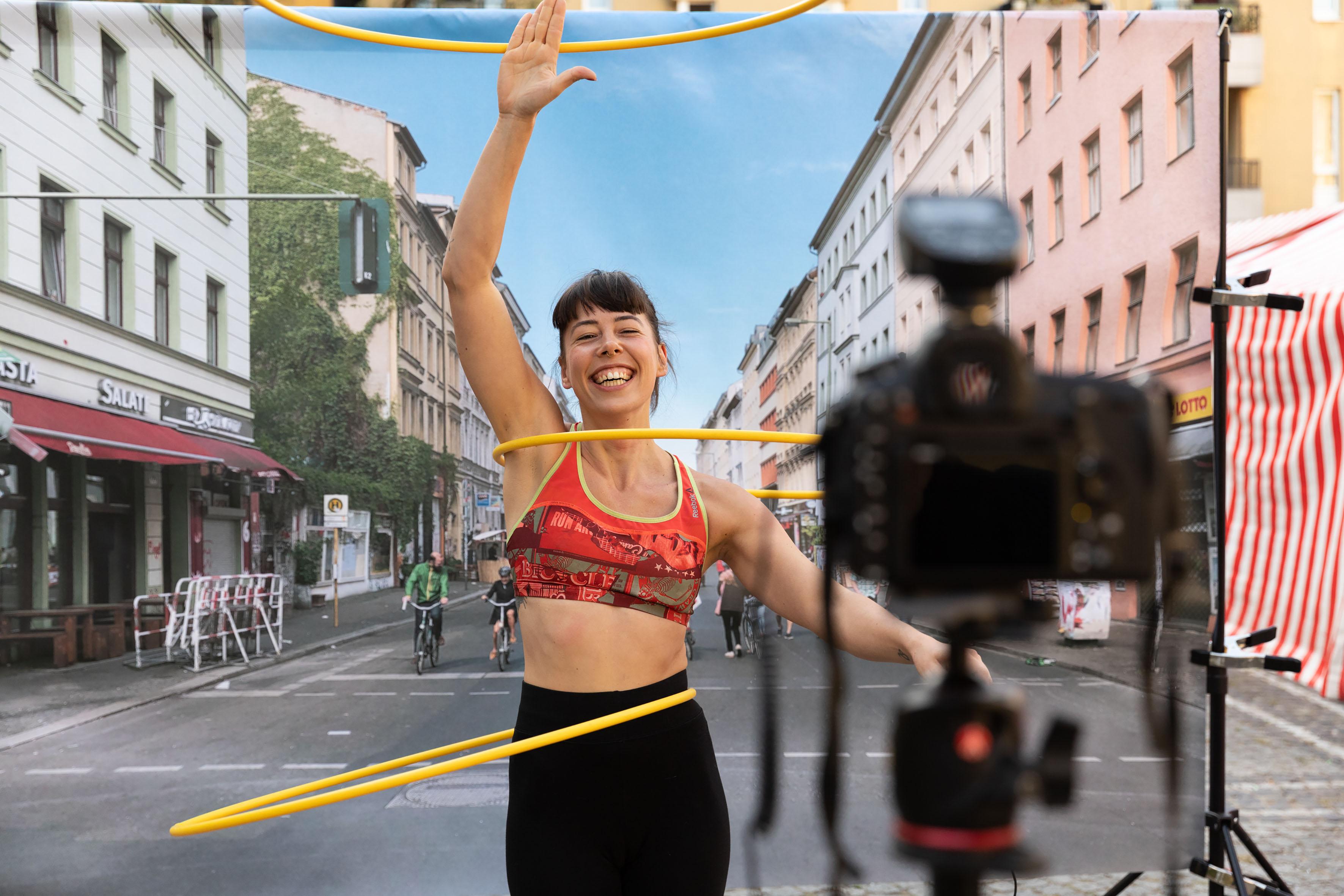 Junge Frau tanzt mit drei Hoola-Hoop-Reifen und lacht dabei.
