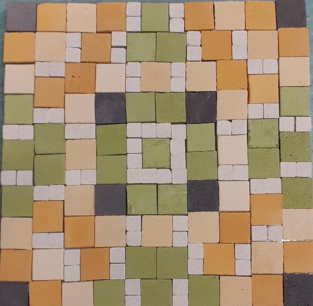 ein Mosaik aus grünen und beigen steinen. Es ergibt ein geometrisches Muster