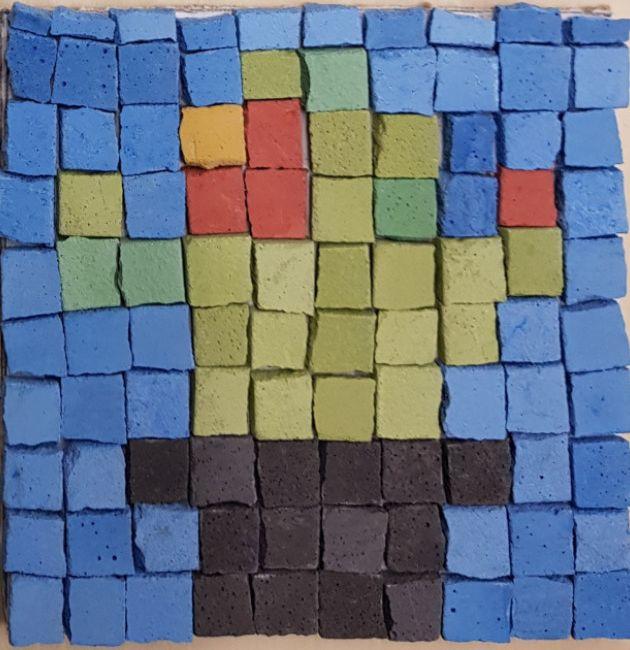 Ein Mosaikbild mit blauen, grünen und schwarzen Steinen. Es soll ein Kaktus sein