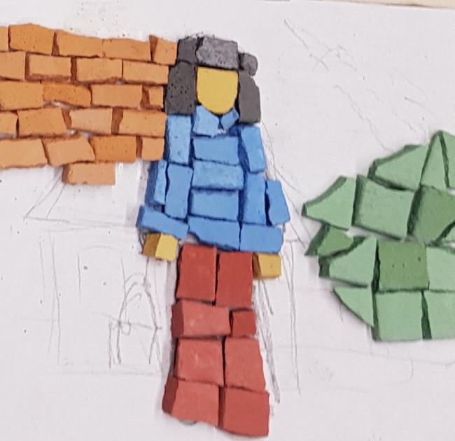 ein halbfertiges Bild aus Steinen. Eine Figur mit roter Hose und blauem Oberteil