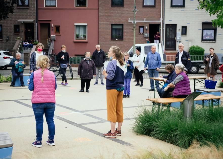 Menschen stehen auf einem kleinen Platz in einem Wohngebiet im Kreis. Sie tragen teilweise Masken. Rechts sitzen zwei ältere Damen auf Bierbänken