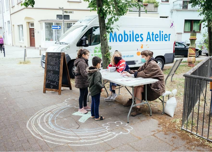 Zwei junge Frauen sitzen hinter einem Klapptisch an einer Straßenecke. Sie tragen Masken. VOr dem Tisch stehen zwei junge kinder. Auf dem Boden ist mit Kreide ein Regenbogen bemalt. Im Hintergrund steht ein Kastenwagen, auf dem ein: Mobiles Atelier steht