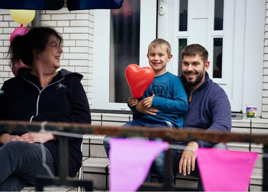 Ein junge sitzt auf dem Schoß eines Mannes, auf den STufen zu einer weißen Haustür. Er hält einen roten Herzballon. Im Vordergrund sitzt eine Frau unter einem Schirm auf einem Stuhl. Sie dreht sich zu den beiden um. Alle drei lachen
