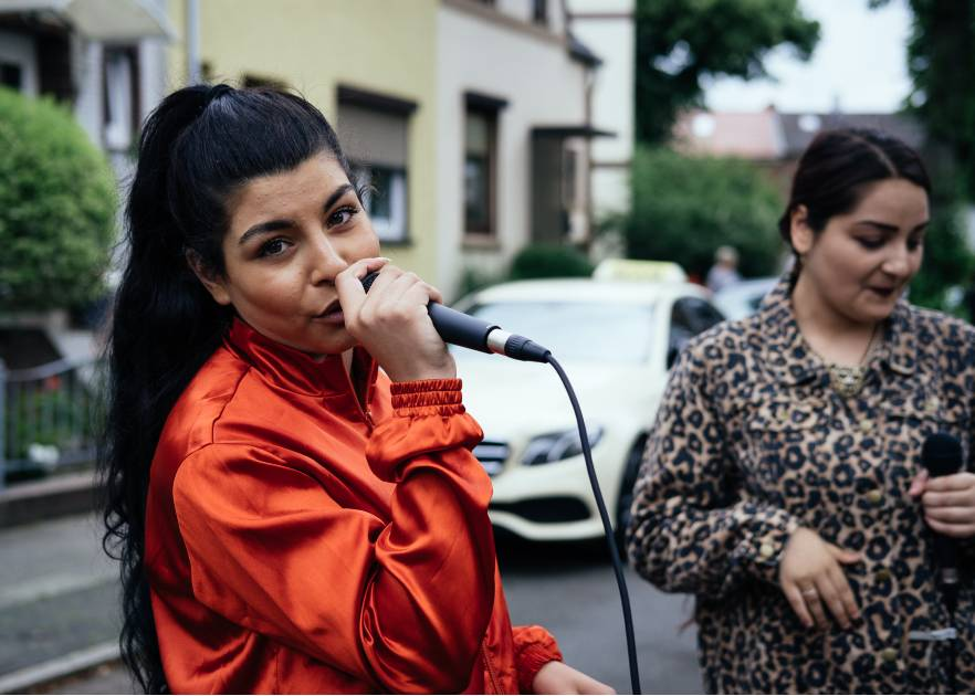 Eine junge Frau mit schaut in die Kamera während sie in ein Mikrofon sing. Sie trägt eine Orange Jacke und hat lange schwarze Haare die zu einem hohen Pferdeschwanz gezogen sind. neben ihr steht eine andere Frau mit Mikrofon, die zur Zeit nicht singt. Sie stehen auf der Straße