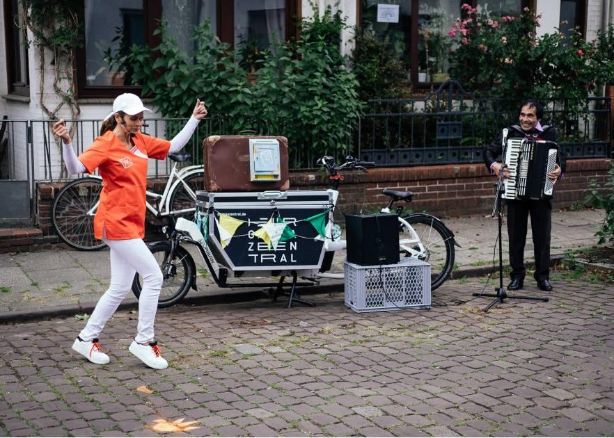 Eine Frau tanzt auf einer Straße mit Kopfsteinpflaster. Sie hat eine weiße Hose, weiße Schuhe, ein weißes langärmliges Shirt und eine weiße Baseballcap an. Darüber trägt sie ein oranges T-Shirt. SIe wird begleitet von einem Mann , der Akkordion spielt. Zwischen ihnen steht ein Kastenfahrrad, welches unter anderem den Lautsprecher trägt. Das Rad steht am Straßenrand. Hinter dem Bürgersteig ist eine kleine Mauer, ein Metallzaun und Vorgartenpflanzen von einem Einfamilienhaus
