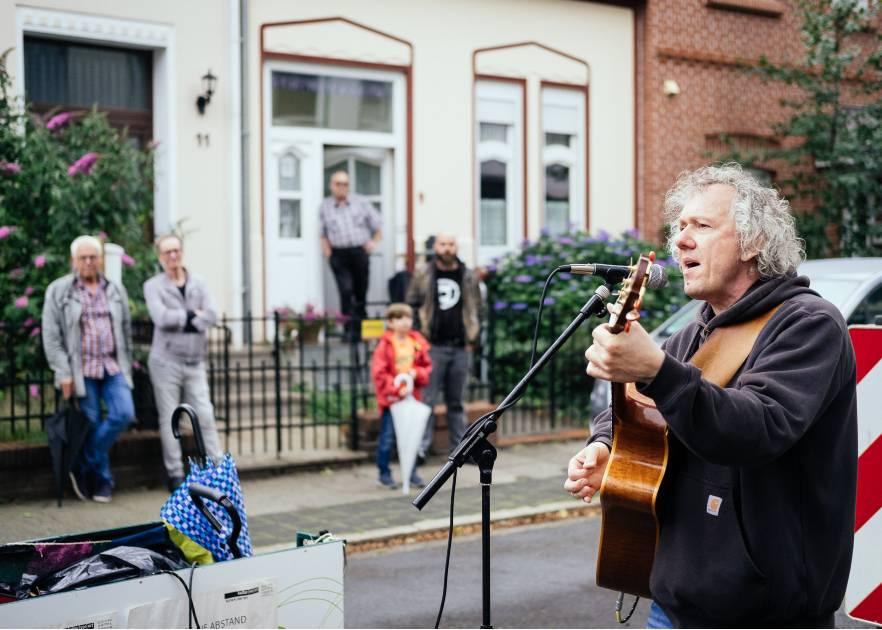Ein Mann mit grauen lockigen Haaren spielt Gitarre und singt. Er steht auf der Straße. Im Hintergrund stehen Menschen an die Zäune gelehnt