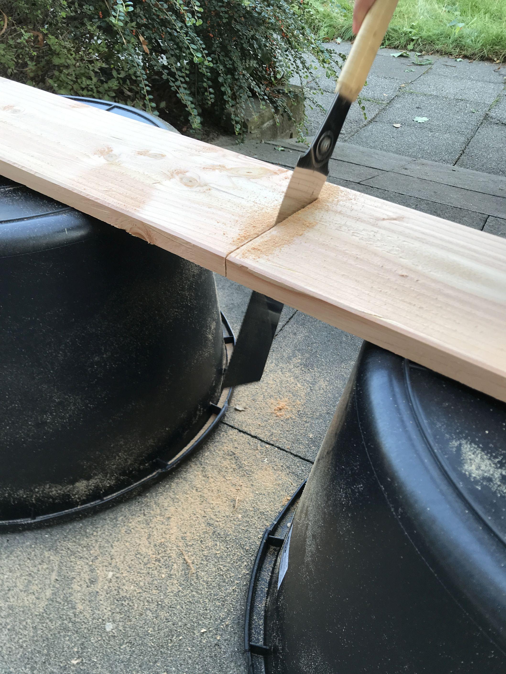 mit einer Säge wird durch ein Holzbrett gesägt, welches auf zwei umgedrehten Eimern liegt