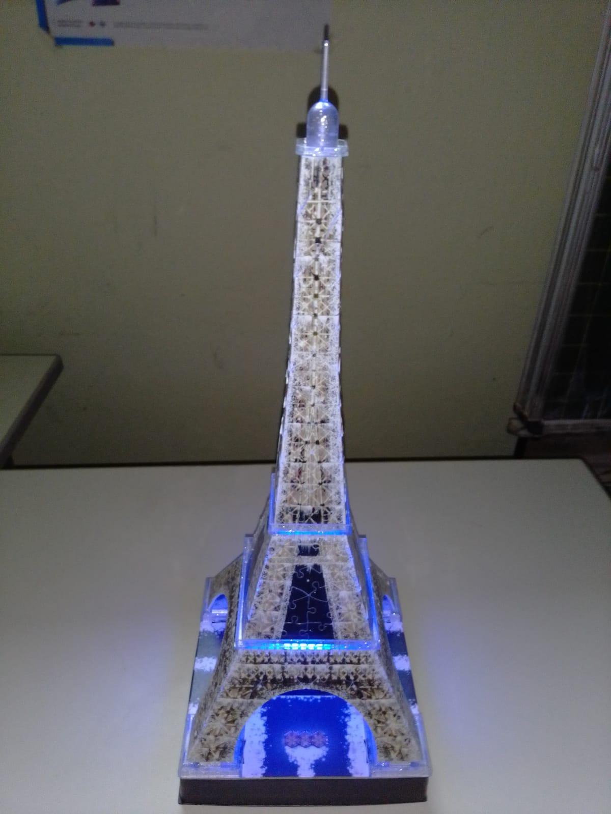 Ein Modell des Eiffelturms aus Holz. Der Turm ist blau erleuchtet.