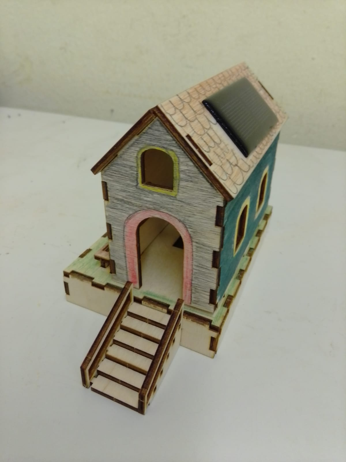 Ein Modell eines Hauses aus Holz. Es hat eine kleine Solarzelle auf dem Dach und ist bemalt