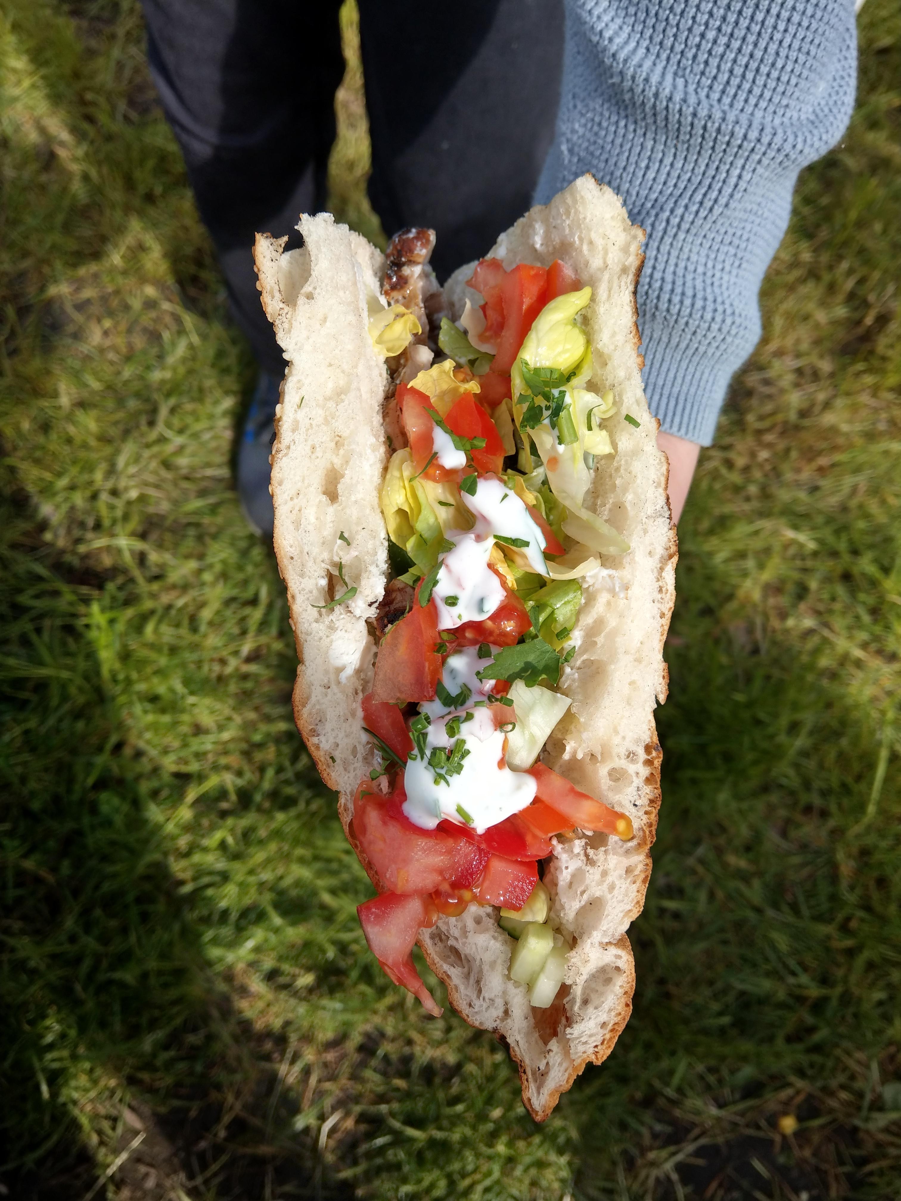 Eine Hand hält einen Döner ins Bild. Dieser ist von oben fotografiert, man sieht das offene Fladenbrot, Salat, Tomaten, weiße Sauce und Kräuter.