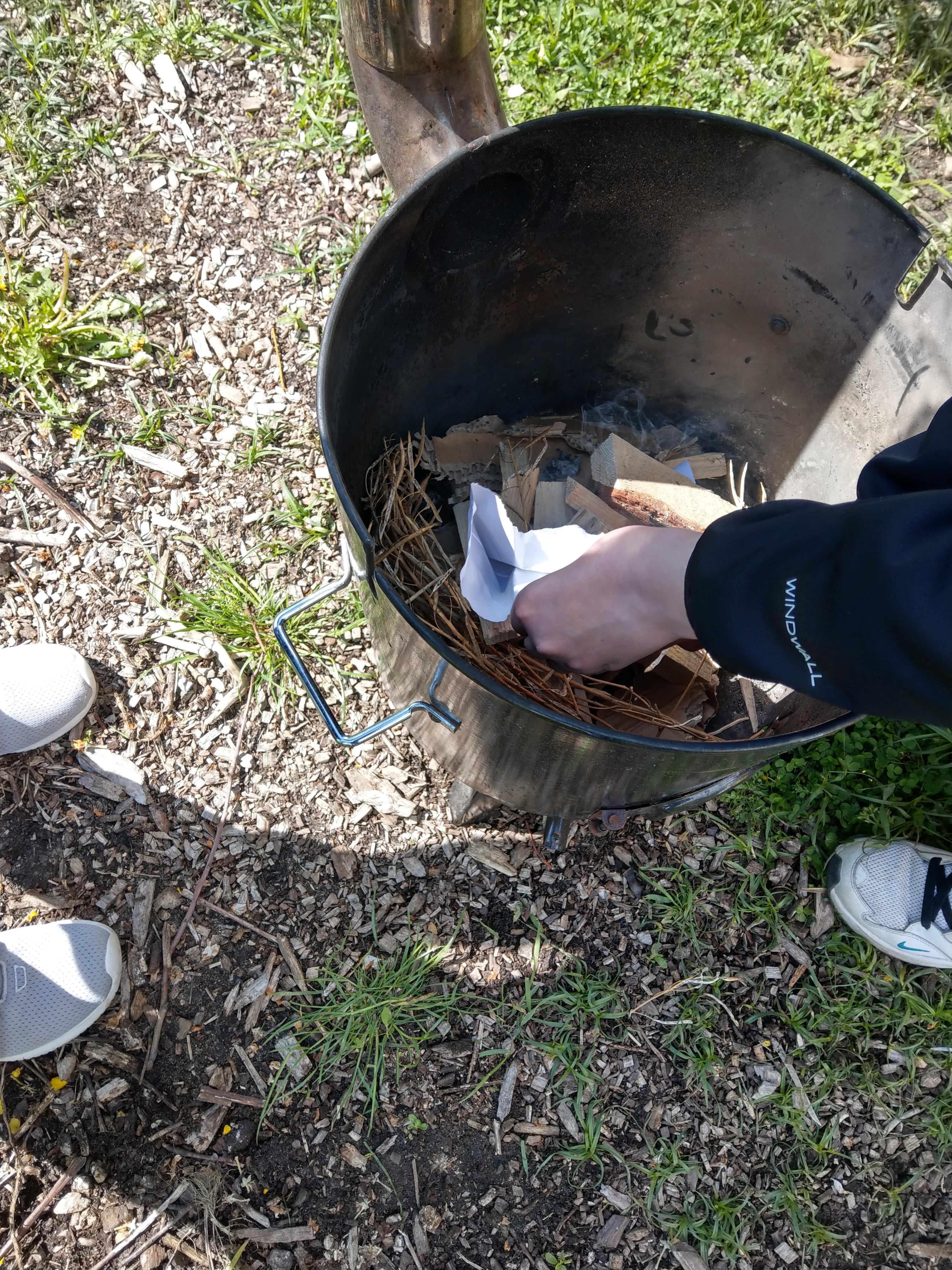 eine Person macht ein Feuer in einem großen Topf aus Metall
