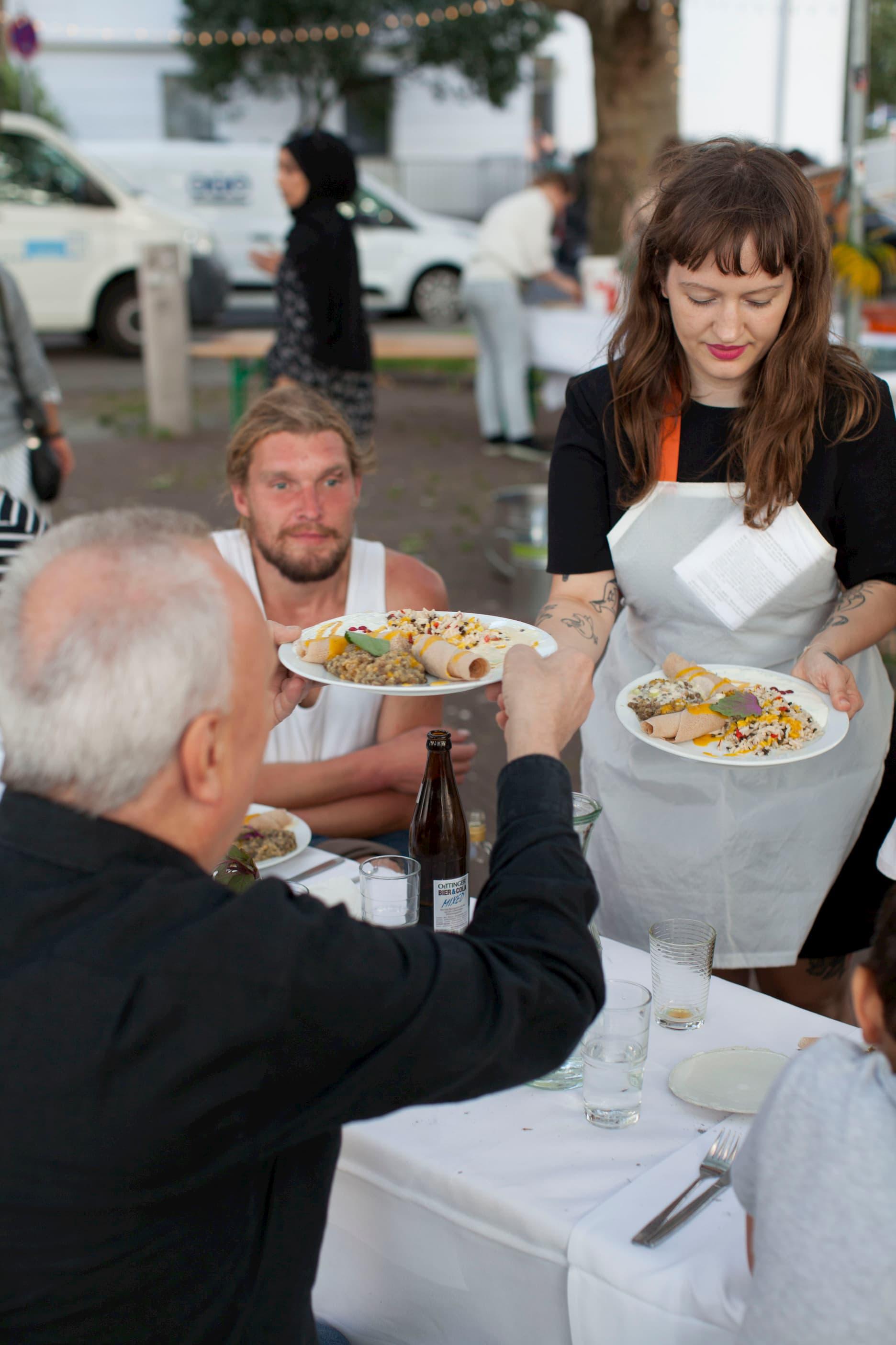 Die Köchin verteilt die befüllten Teller an einen älteren Herr. Das Essen ist unidentifizierbar, aber bunt und sieht einladend aus.