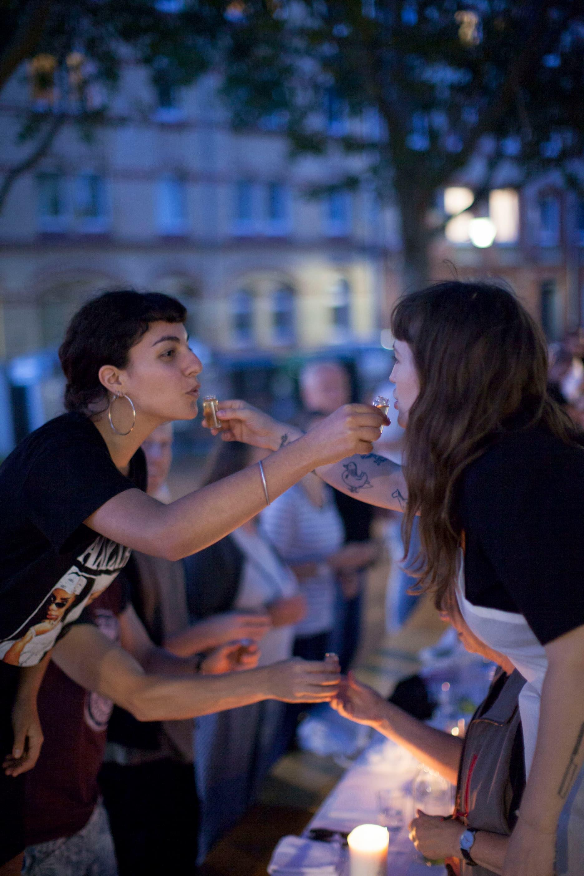Die Köchin und eine junge Frau verabreichen sich gegenseitig einen Schnaps.