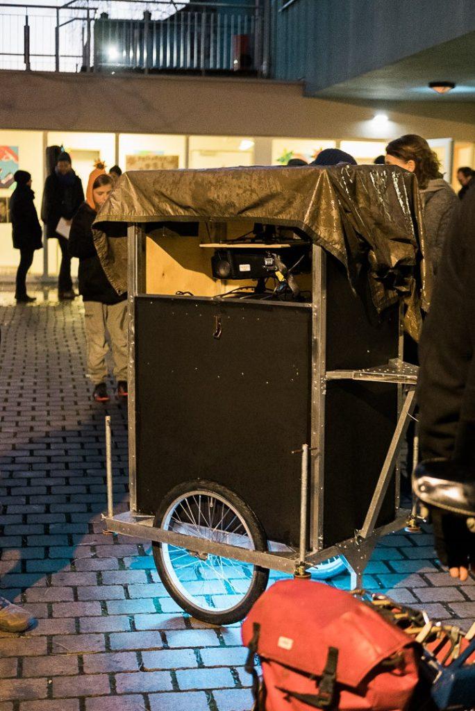 Das fertige Mpbil steht auf einem Platz draußen. Eine Plastikplane schützt die Technik vor Regen.