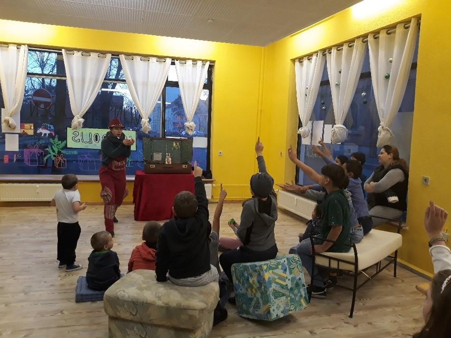 Kinder sitzen in einem Halbkreis um das Koffertheater herum. Die Schauspielerin steht neben dem Koffer und gibt ihre Darbietung