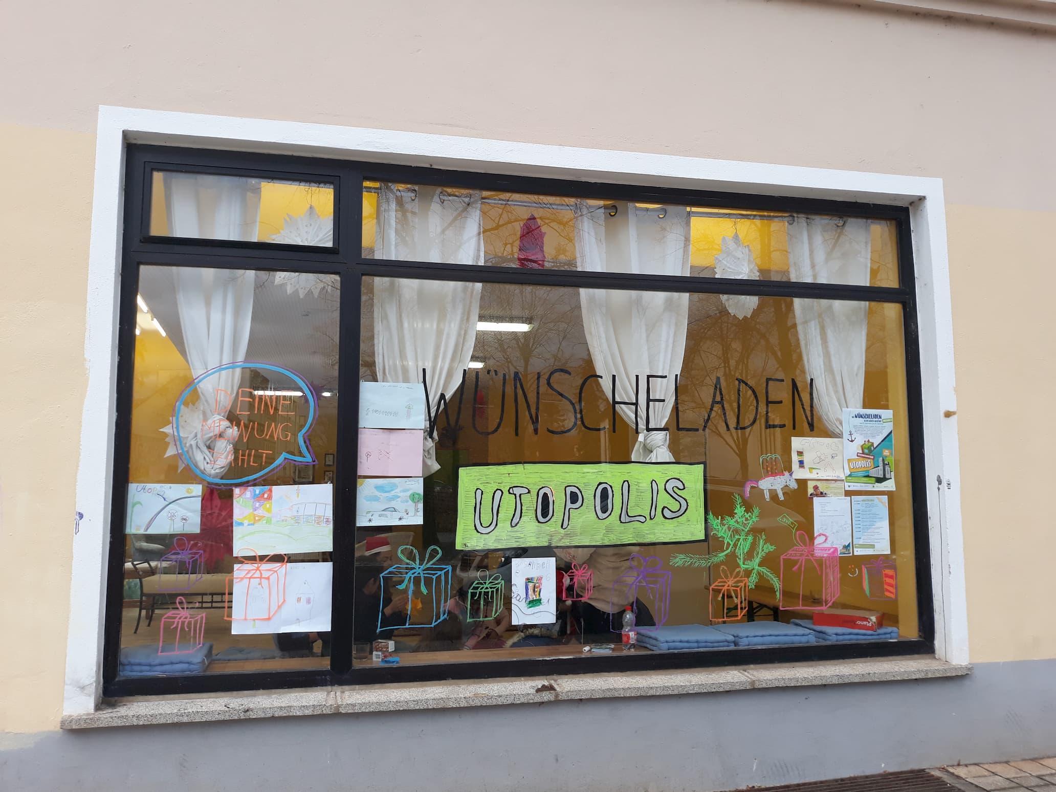 """Ladenfenster des Wünscheladens UTOPOLIS. Mit Fingerfarben wurde Geschenke und eine Sprechblase aufs Fenster gemalt. In der Sprechblase steht """"deine Meinung zählt""""."""
