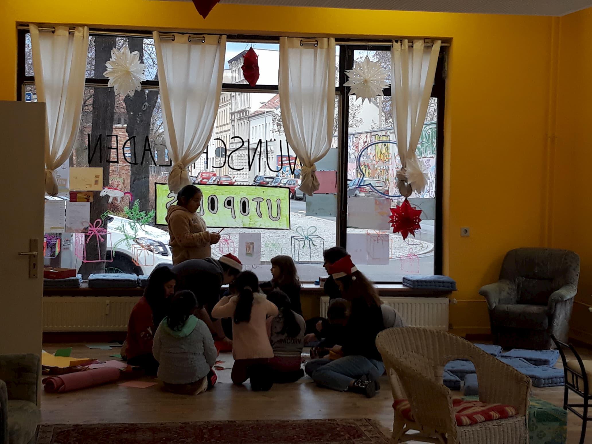 Kinder sitzen im Wünscheladen auf dem Boden