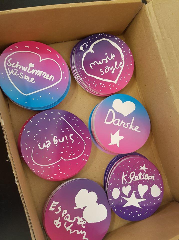 6 Stapel mit Stickern in einer Pappkiste. Die Sticker sind rund, pink, blau und lila. Darauf stehen in Handschrift Wörter in unterschiedlichen Sprachen: Singen, Klettern, Danse, Yüsme
