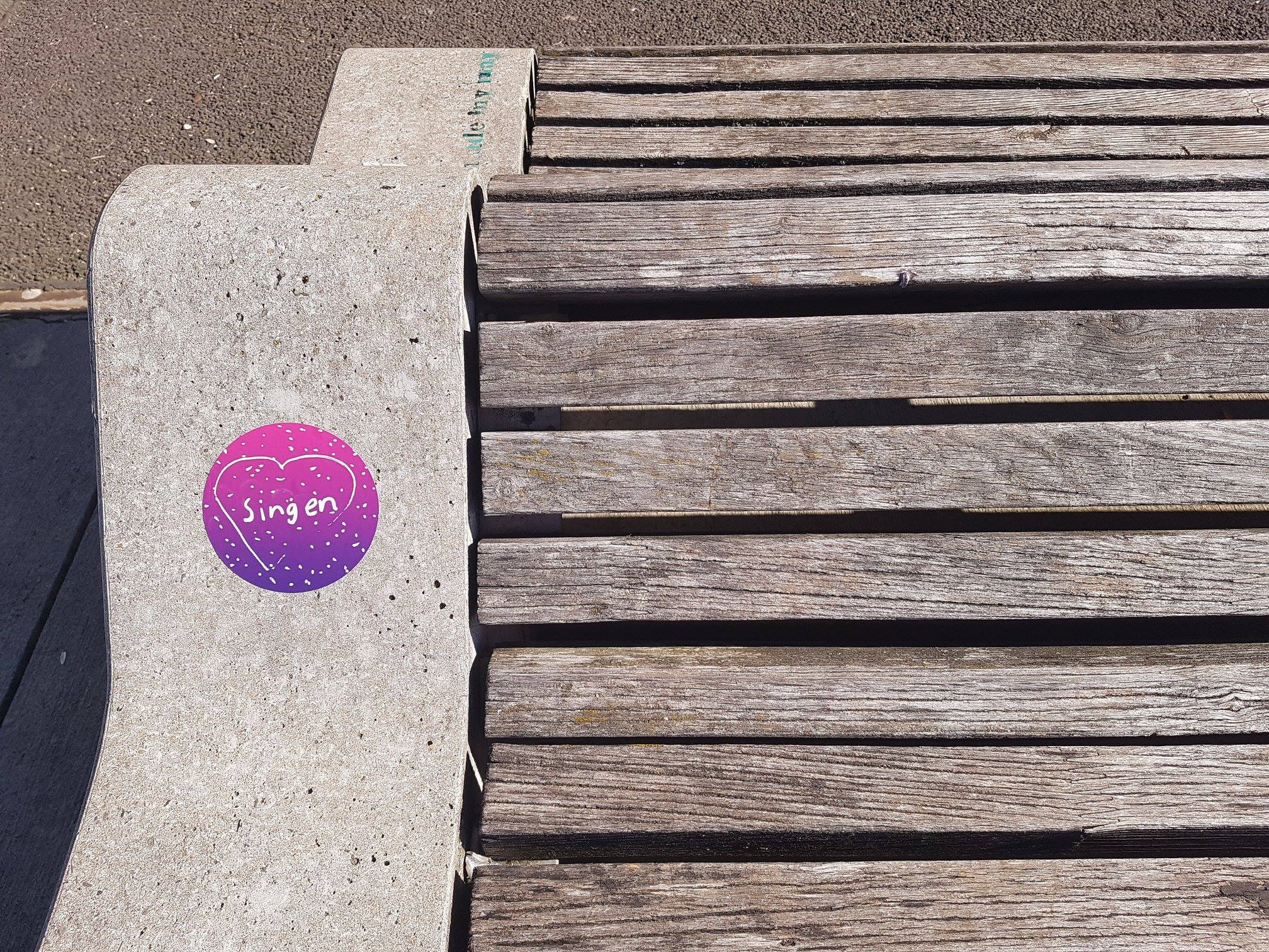 """Ein pinker Aufkleber mit der Aufschrift """"Singen"""" klebt auf einer Bank in der Sonne."""