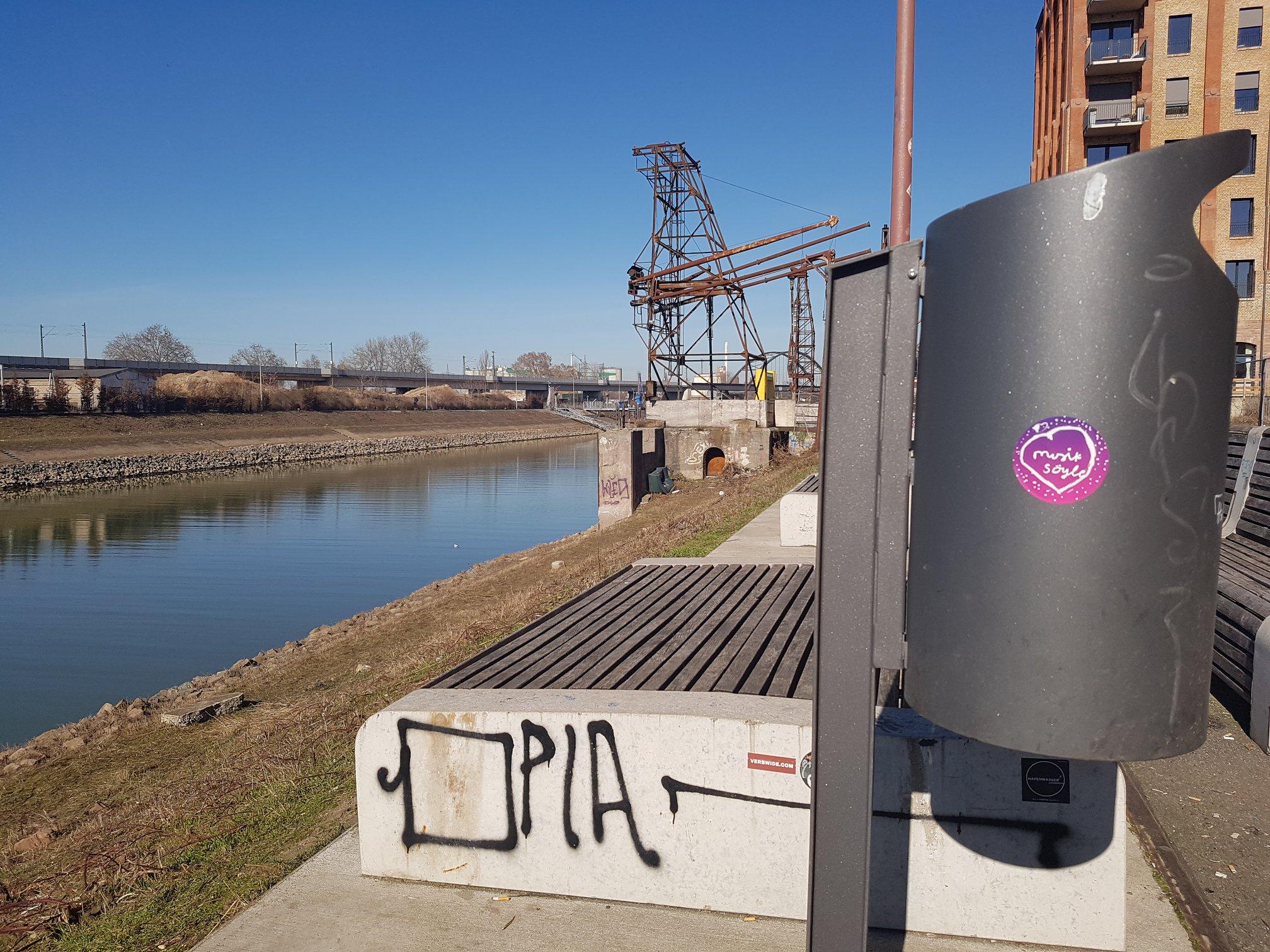 """Ein runder pinker Aufkleber mit der Aufschrift """"Musik/ Söyle"""" klebt auf einem Mülleimer an der Promenade am Mannheimer Verbindungskanal"""