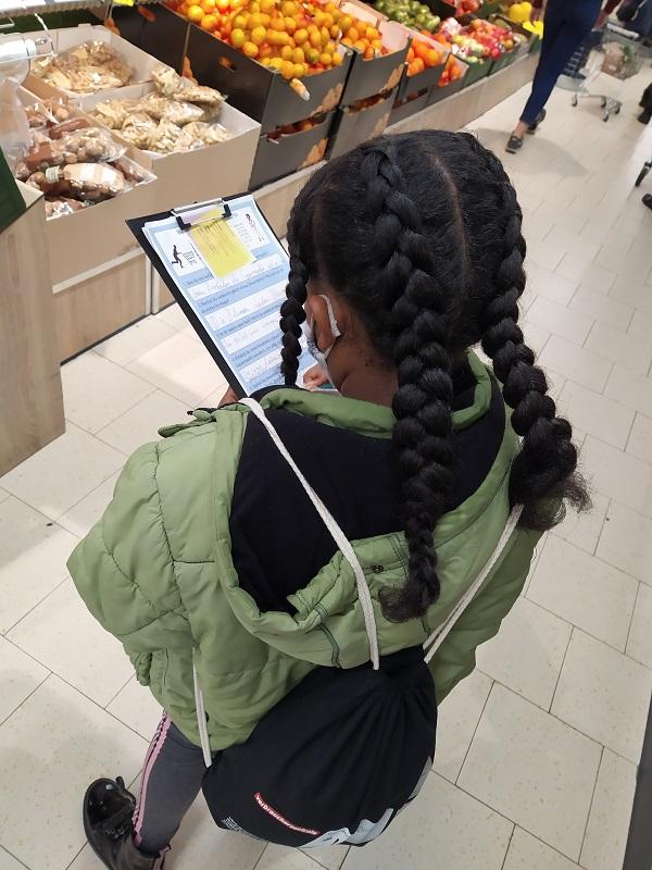 ein Mädchen steht in einem Supermarkt in der Gemüseabteilung und füllt einen Fragebogen auf einem Klemmbrett aus. Sie ist von hinten oben aufgenommen, sodass ihr Gesicht nicht sichtbar ist. Sie hat eine grüne Winterjacke an, einen schwarzen Turnbeutel, eine Maske auf und ihr schwarzes Haar ist in vier dicke Zöpfe geflochten.