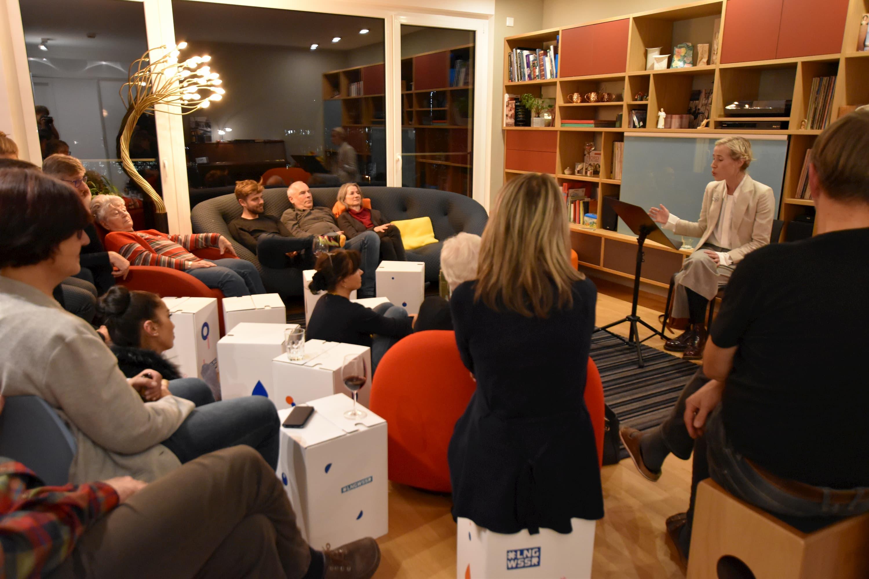 Die Nachbarn sitzen gemeinsam im Wohnzimmer auf den Sofas des Gastgebers, aber auch auf mitgebrachten Papphockern. Eine Künstlerin liest oder singt gerade
