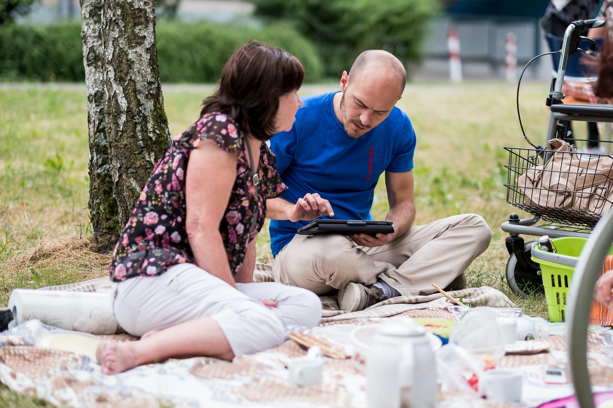 Der Betreuer der Befragung sitzt gemeinsam mit einer Frau im Park auf einer Decke und erklärt ihr die Funktionen des Tablets