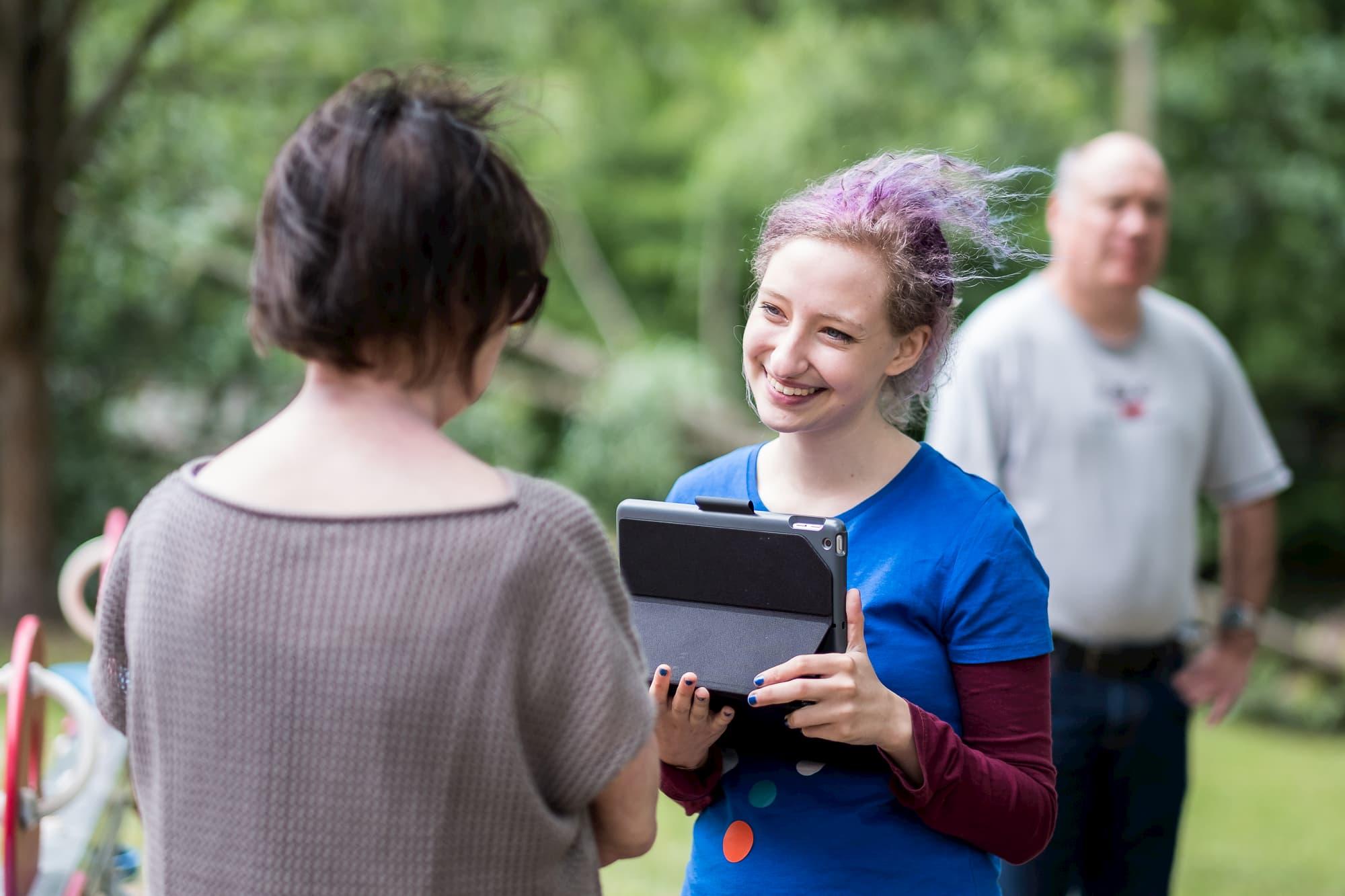 Eine Mitarbeiterin unterhält sich mit einer Bürgerin und hält dabei das Befragungs-Tablet in der Hand