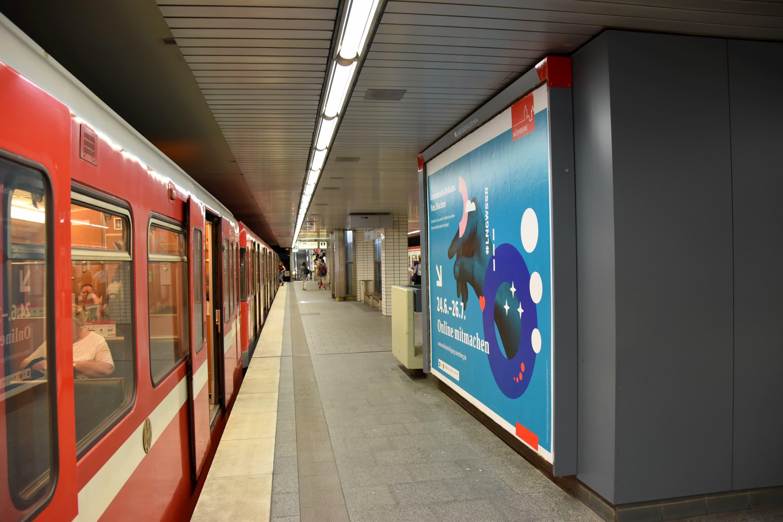 Ein Plakat in einer unterirdischen S-Bahnstation. Das Plakat fordert die Bürger auf, bei der Online-Befragung mitzumachen.