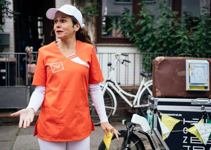 Eine Frau mit orangem Tshirt steht auf der STraße
