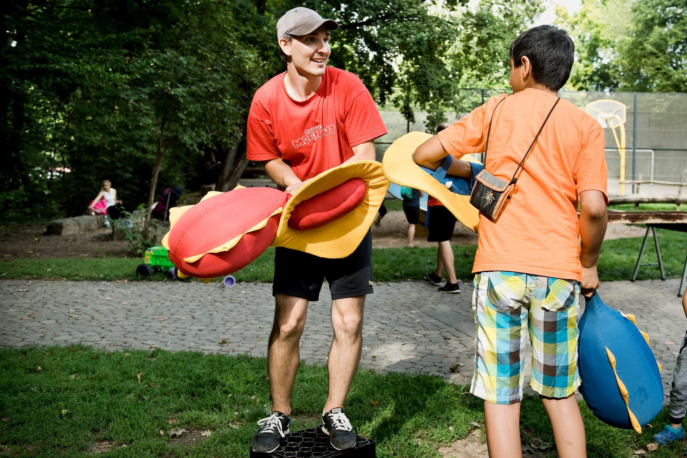 Der Jugendsozialarbeiter spielt mit einem Jugendlichen und Stofftieren in einem Park