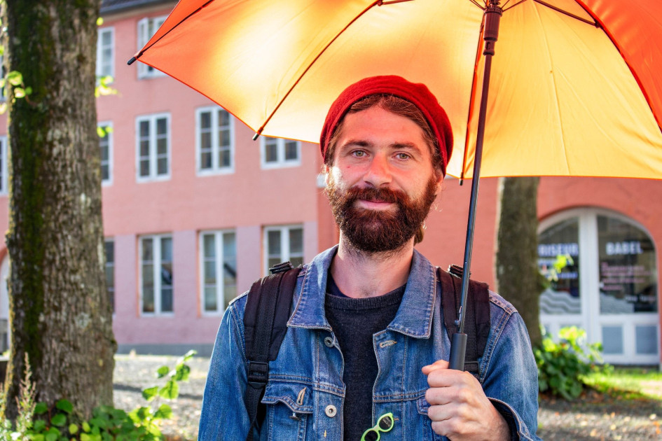 Ein junger Mann mit braunem Bart und roter Mütze hät einen orangen Regenschirm. Er hat trägt einen Rucksack und eine blaue Jeansjacke