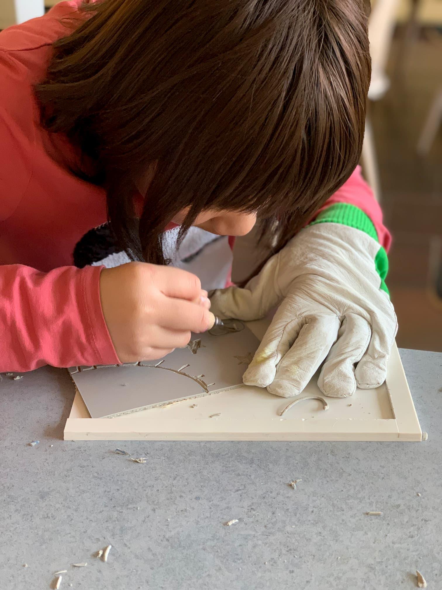 Ein Kind konzentriert sich ganu genau auf die Arbeit an der Linolplatte. Zur Sicherheit trägt es einen Handschuh an der Hand, die die Platte festhält.