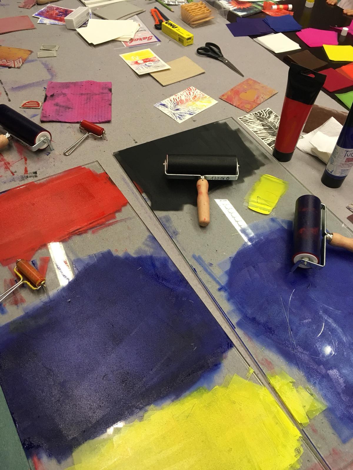 Arbeitstisch mit Linolplatten, ersten Drucken, Farbwalzen, Farbtuben und anderlei Bastelutensilien
