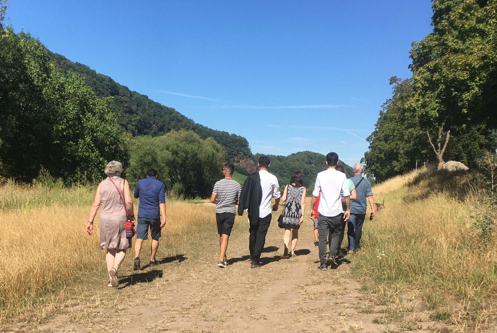 eine Gruppe von Menschen ist von hinten aufgenommen. Sie gehen neben- und hintereinander einen Weg durch ein Tal entlang. Das vorhandenen Gras ist von der Sonne getrocknet. Rechts und links ziehen sich grüne Bäume die Hänge hoch. Der Himmel ist knallblau.