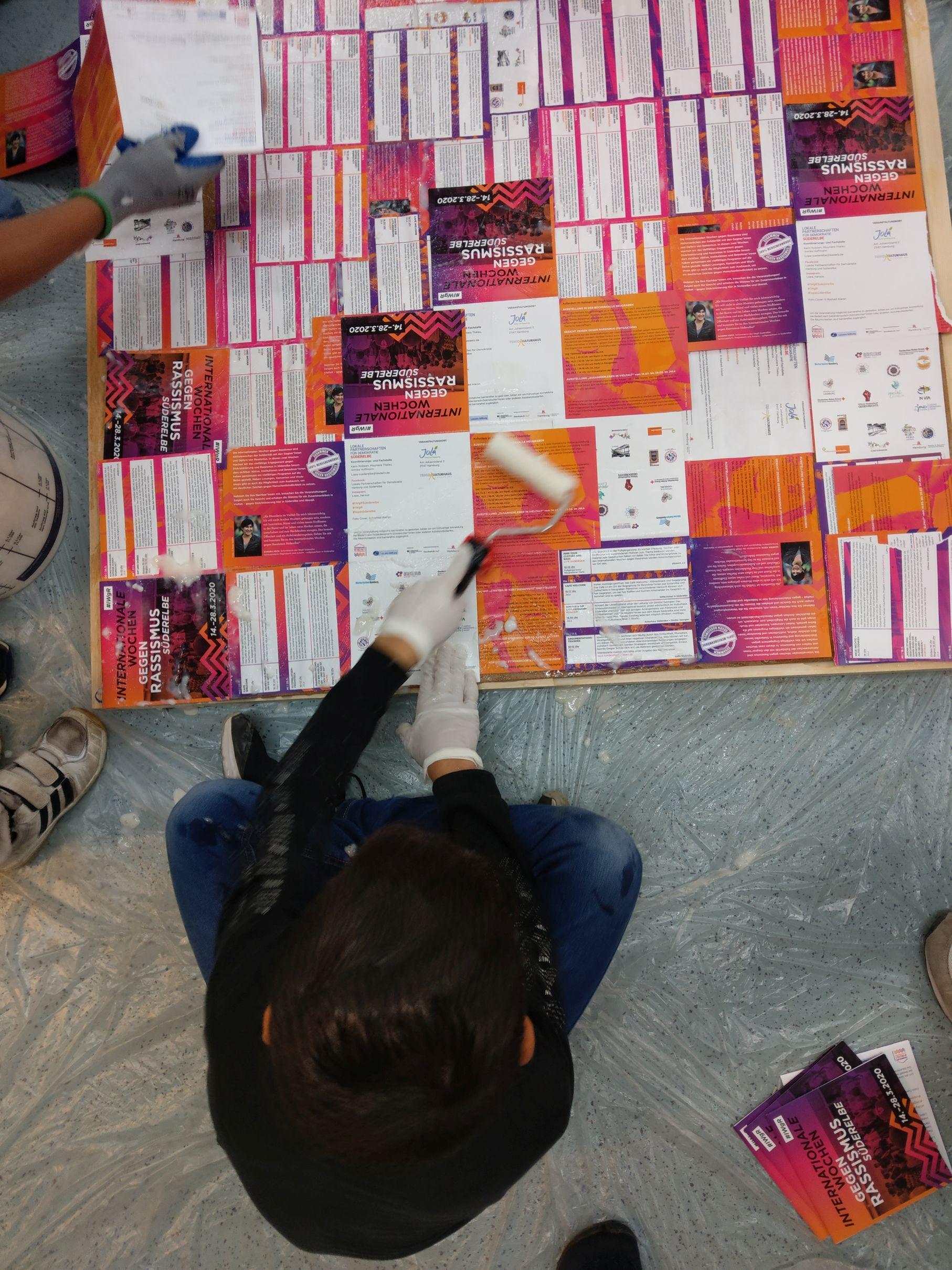Eine Person sitzt auf dem Boden im Schneidersitz und bestreicht eine Platte mit Leim. Das Bild ist direkt von oben aufgenommen, sodass man der Person auf den SCheitel schaut. Auf die Platte sind viele Flyer gleicher Art aufgeklebt. sie sind orange und lila