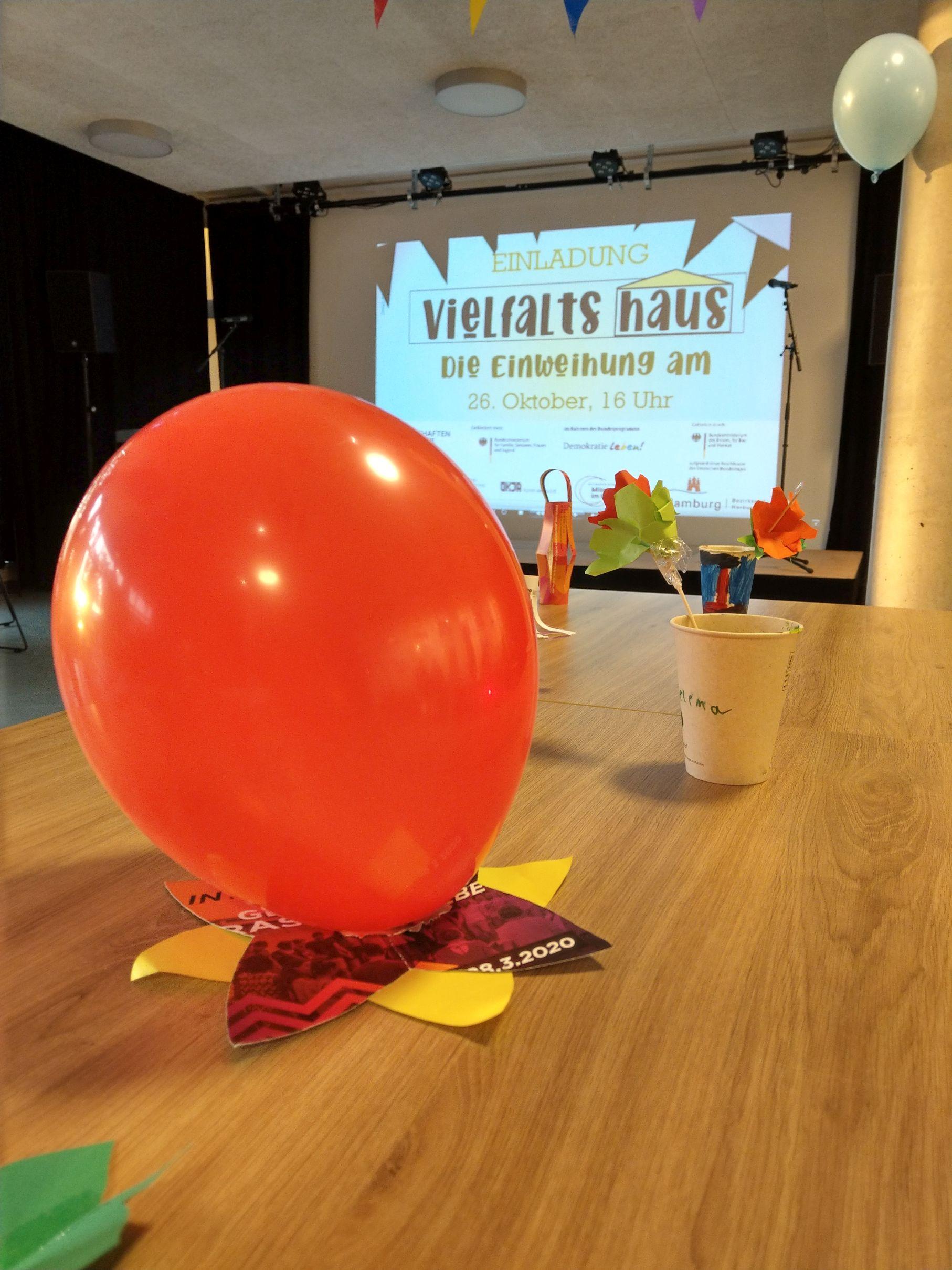 Foto von der Einweihung des Vielfalthauses. Im Vordergrund ein oranger Luftballon auf einem Tisch. Im Hintergrund auf einer Leinwand eine Folie von einer Präsentation