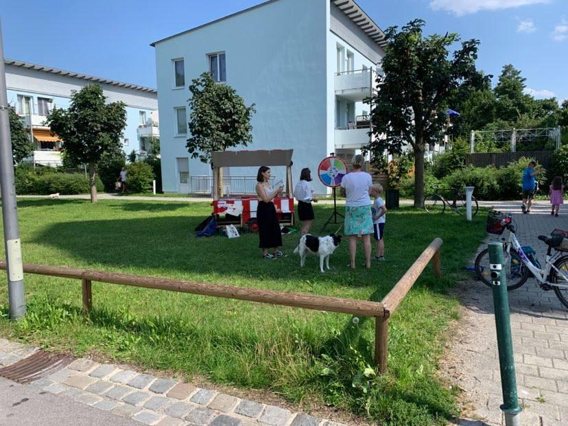 Der Infostand steht auf einer Rasenfläche vor einigen weißen Mehrfamilienhäusern