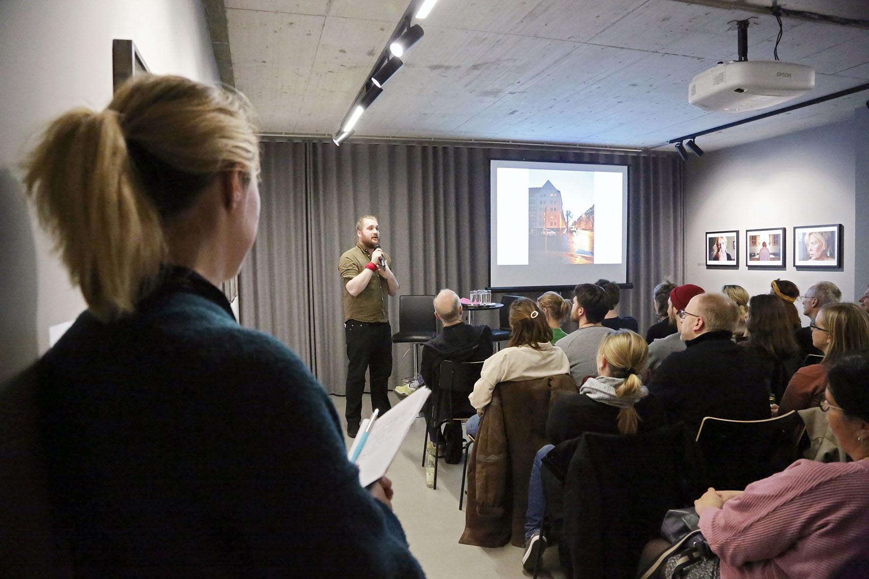Ein Vortragender steht neben der Leinwand, auf die ein Bild projiziert ist und erklärt dazu.