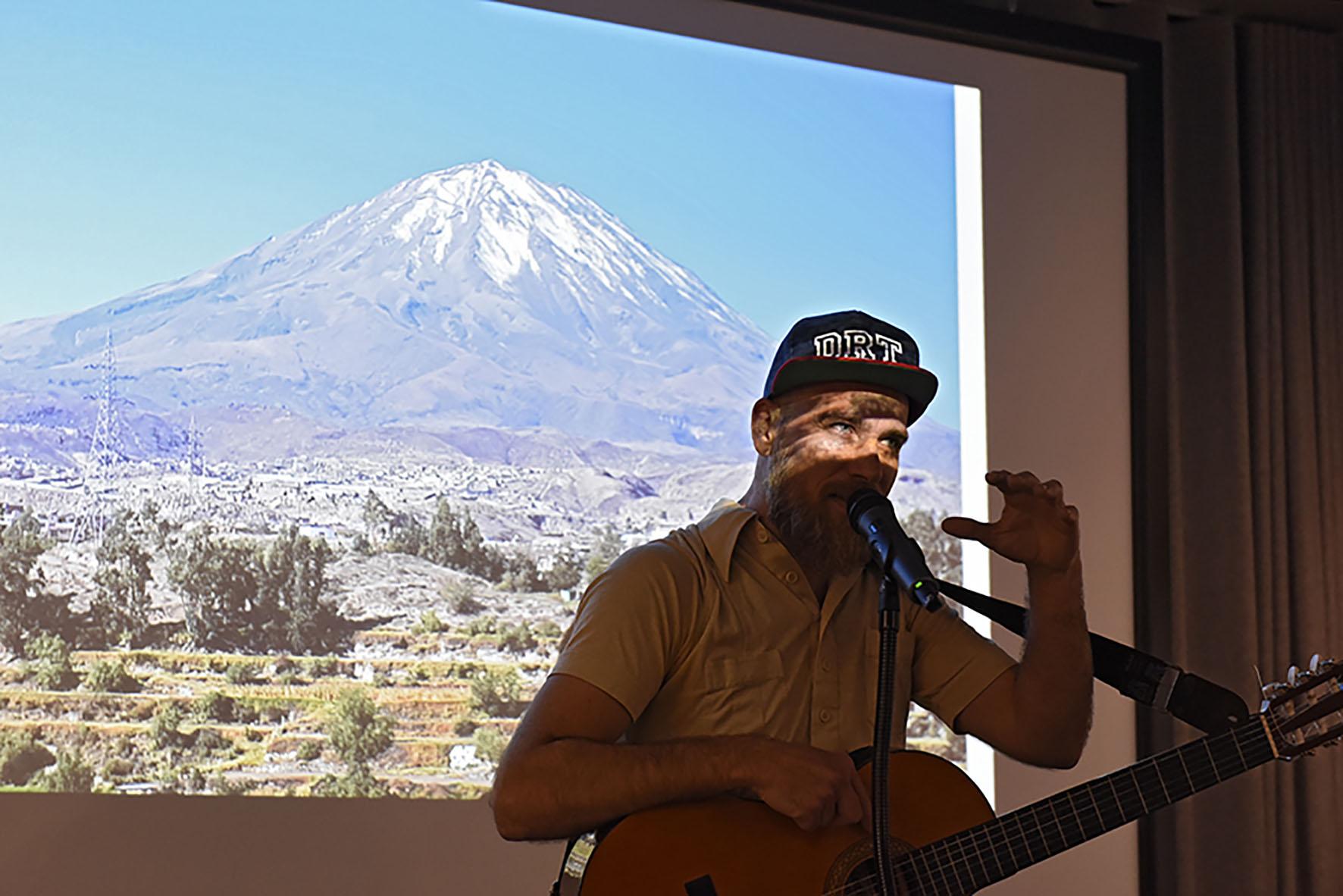 Ein Sänger mit Gitarre steht vor der Leinwand, auf die ein Foto eines Vulkans projiziert ist.