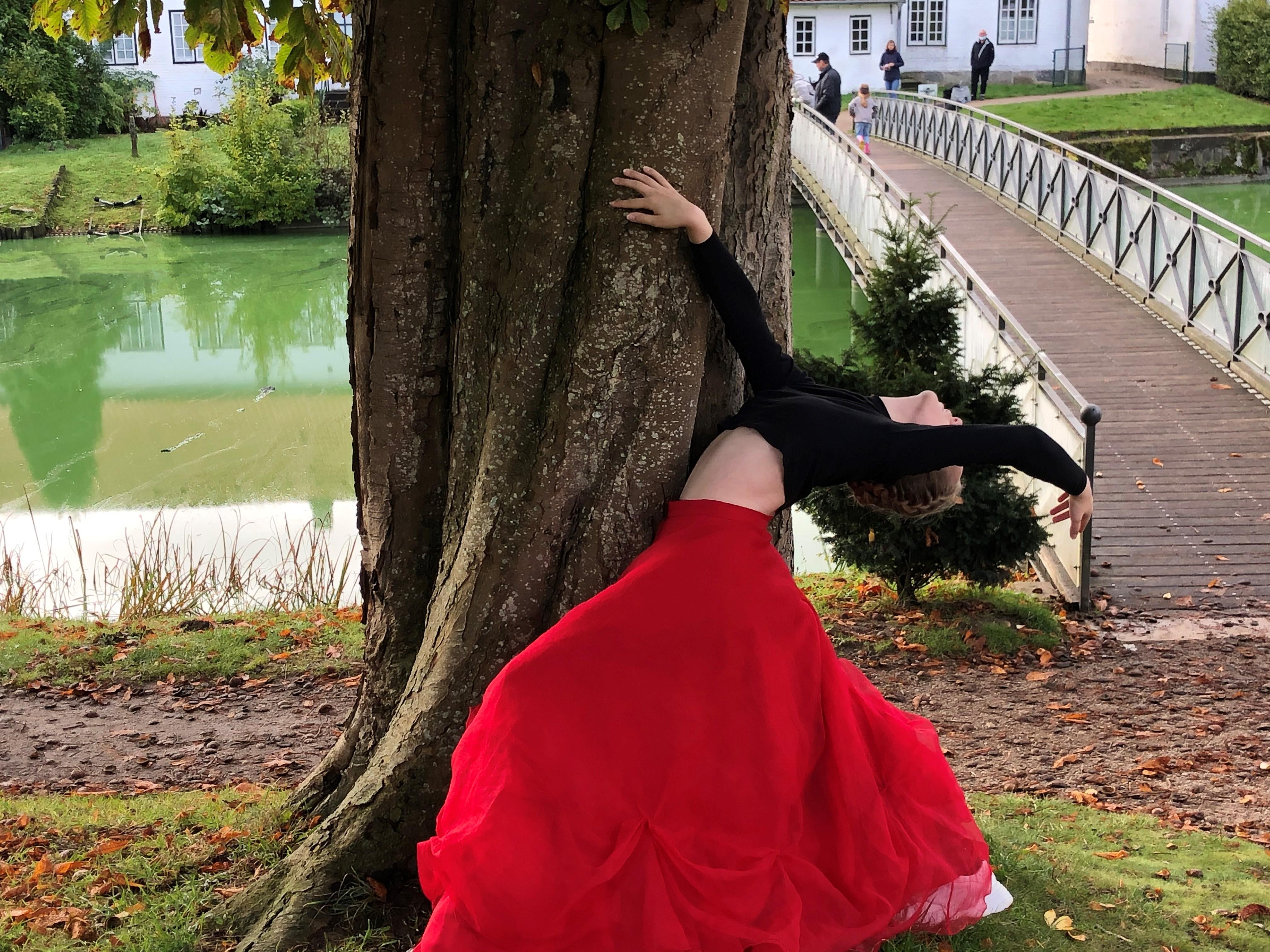 eine junge Frau hält sich bei einer Tanzpose an einem dicken Kastanienbaum fest. Sie hat einen langen, knallroten Rock an sowie ein langärmliges, bauchfreies schwarzes Oberteil. Ihr Oberkörper ist anmutig weit nach hinten gebogen, und ihr Kopf in den Nacken gelegt. Im Hintergrund ein Fluss und eine Fußgängerbrücke