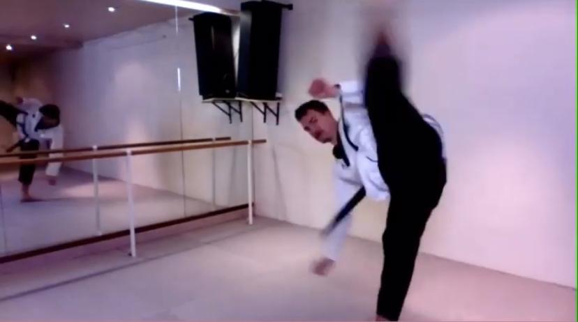 Ein Mann in Kampfsportanzug tritt in die Luft. Er steht in einem Trainingsraum. An der hinteren Wand befindet sich ein großer Spiegel über den man den Mann von hinten sieht.