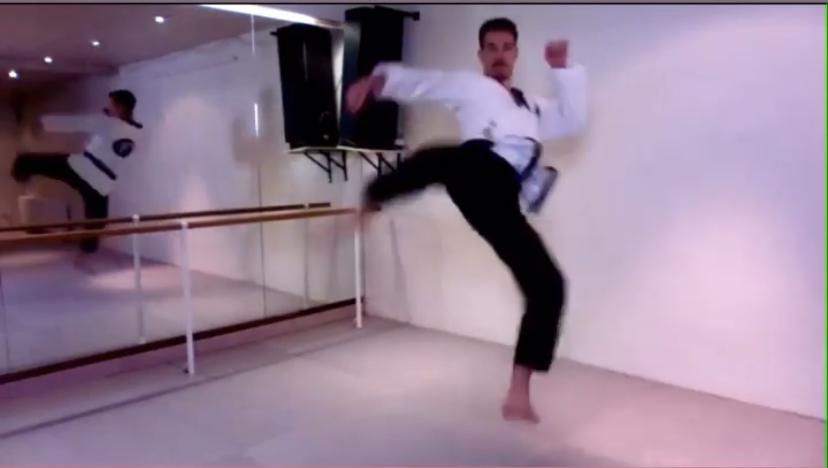 Ein Mann in Kampfsportanzug springt tretend in die Luft. Er steht in einem Trainingsraum. An der hinteren Wand befindet sich ein großer Spiegel über den man den Mann von hinten sieht.